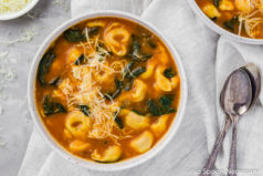 Overhead shot of a bowl of Easy Chicken, Spinach & Tortellini Tomato Soup on a gray surface and neutral colored linen with two spoons next to the bowl and an additional bowl of soup and small bowl of shredded cheese tucked in the upper corners of shot.