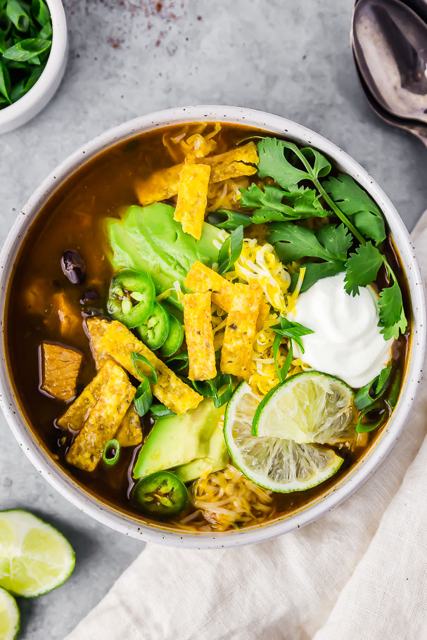 Overhead shot of a white bowl containing Easy Southwestern Chicken & Black Bean Soup topped with sliced avocados, cilantro, tortilla strips and a dollop of sour cream; with a neutral linen, lime wedges, scallions and 2 spoons surrounding the bowl.
