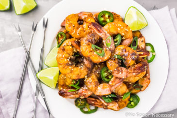 Overhead shot of a white plate filled with Spicy Honey Glazed Skillet Shrimp, lime wedges, jalapeno slices, and sliced scallions with a purple linen, seafood forks and lime wedges surrounding the plate.
