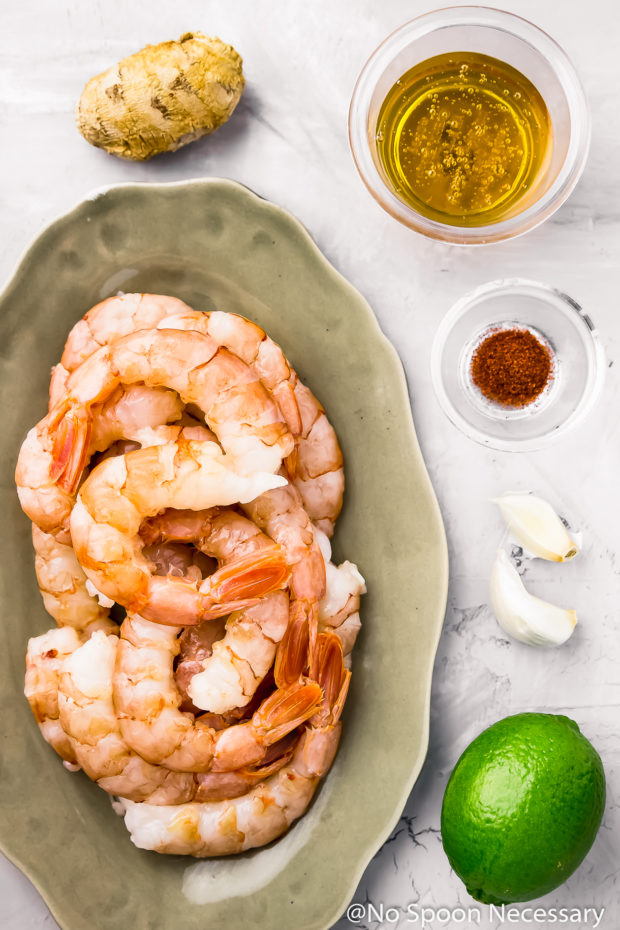 Overhead shot of all the ingredients needed to make Spicy Honey Glazed Skillet Shrimp neatly organized on a bluish-gray surface.