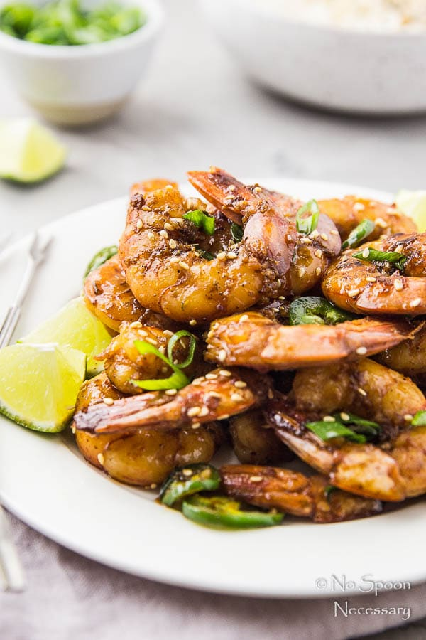 Straight on shot of a white plate filled with Spicy Honey Glazed Skillet Shrimp, lime wedges, jalapeno slices, and sliced scallions with a bowl of rice, ramekin of scallions and lime wedge blurred in the background.