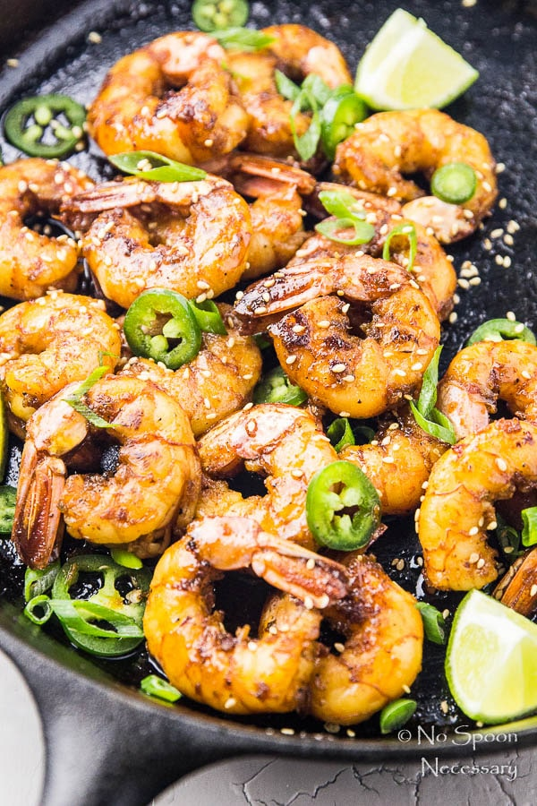Angled, overhead shot of a cast iron skillet filled with Spicy Honey Glazed Skillet Shrimp, lime wedges, jalapeno slices, and sliced scallions.