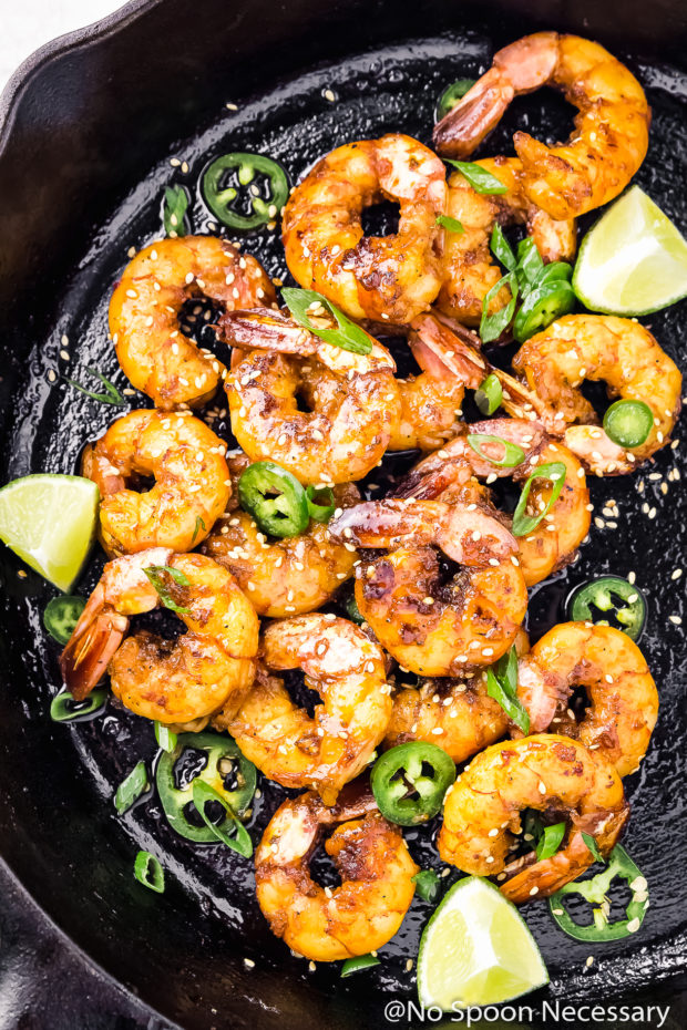 Overhead shot of a cast iron skillet filled with Spicy Honey Glazed Skillet Shrimp, lime wedges, jalapeno slices, and sliced scallions.