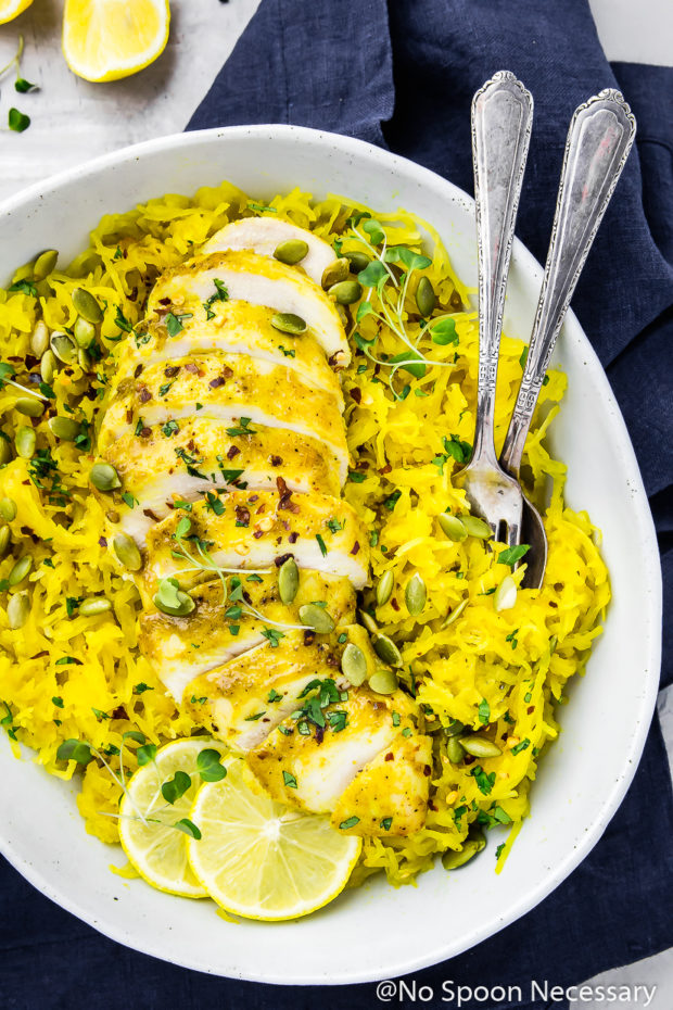 Overhead shot of Baked Curried Chicken & Spaghetti Squash in a neutral colored serving bowl and a spoon and fork inserted into the squash with a blue linen underneath the bowl and lemon wedges in the upper left corner of the shot.