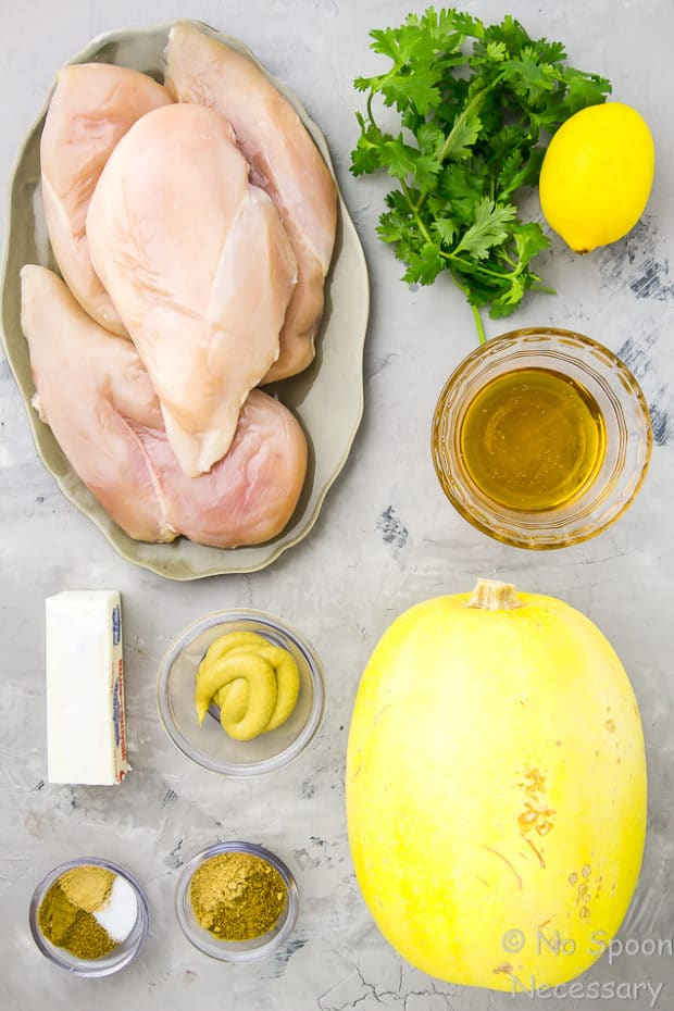 All the ingredients needed to make Sheet Pan Baked Curried Chicken & Spaghetti Squash neatly organized on a gray plaster surface.