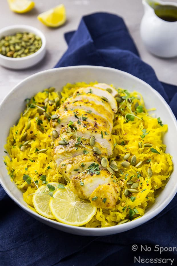 Angled shot of Baked Curried Chicken & Spaghetti Squash in a neutral colored serving bowl with a blue linen underneath the bowl and honey curry dressing, a ramekin of pumpkin seeds and lemon wedges blurred behind the bowl.