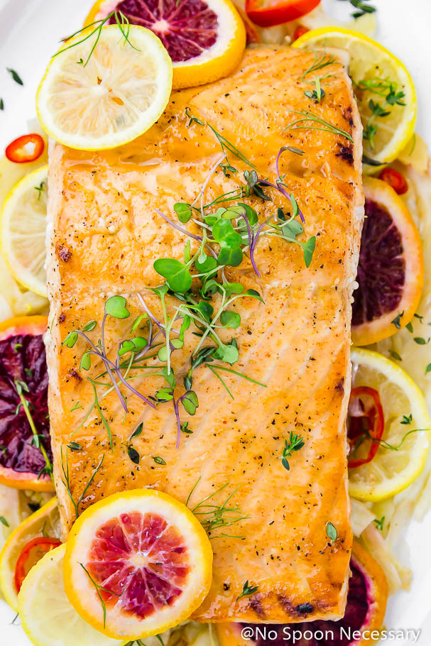 Overhead, up-close shot of a white platter containing slices of roasted fennel, blood oranges and lemons topped with a center cut Citrus & Honey Roasted Salmon filet garnished with microgreens.