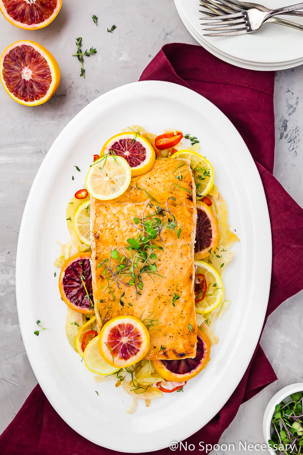 Overhead shot of a white platter containing slices of roasted fennel, blood oranges and lemons topped with a center cut Honey & Citrus Roasted Salmon filet garnished with microgreens. There are a stack of white plates, forks, blood orange halves, thyme sprigs, maroon linen and ramekin of microgreens surrounding the platter.