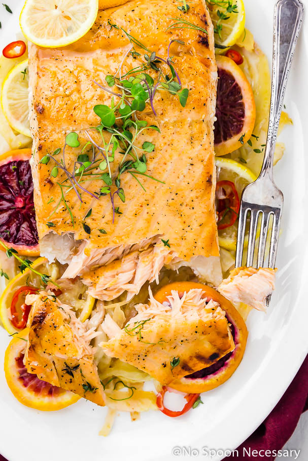 Overhead shot of a white platter containing a fork and partially flaked apart Citrus & Honey Roasted Salmon filet on a bed of slices of roasted fennel, blood oranges and lemons, garnished with microgreens.