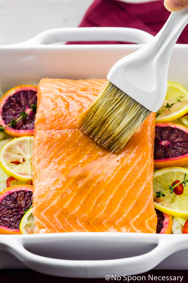 45 degree angle shot of a square white baking dish filled with slices of blood oranges, lemons, sprigs of thyme and topped with a raw center cut filet of salmon and a pastry brush applying a Citrus Honey marinade to the salmon. {prior to roasting}