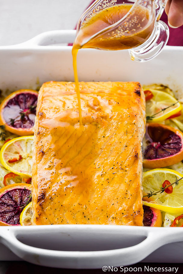 45 degree angle shot of a square white baking dish filled with slices of blood oranges, lemons, sprigs of thyme and topped with a Citrus Honey Roasted Salmon filet and a hand pouring on a citrus honey sauce on top of the salmon.