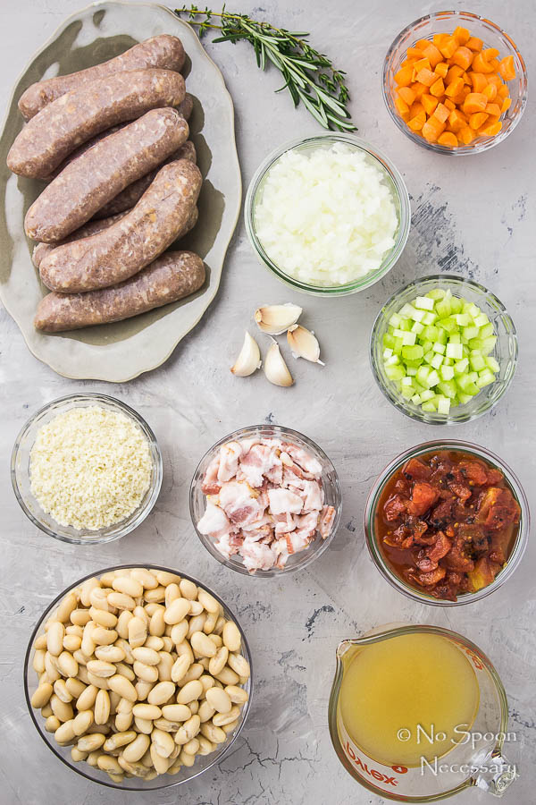 Overhead shot of all the ingredients needed to make Chicken Apple Sausage Quick Cassoulet neatly organized in individual bowls on a gray surface.