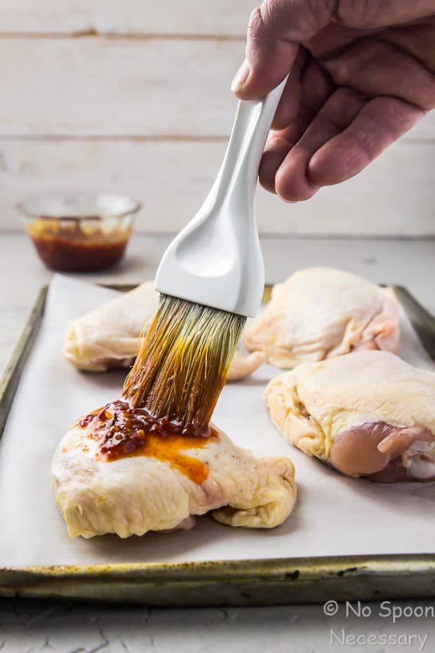 Straight on shot of sheet pan of chicken thighs, with a hand holding a pastry brush and brushing harissa marinade on a single chicken thigh.