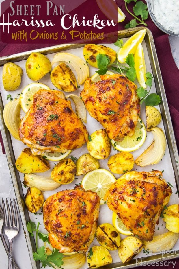 Overhead shot of a sheet pan of Harissa Chicken with Onions & Potatoes on a red linen with a fork and spoon in the bottom corner and a glass bowl of yogurt in the upper corner of the shot.