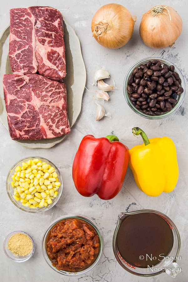 Overhead shot of all the ingredients needed to make Slow Cooker Beef Fajita Soup neatly arranged on a gray surface.