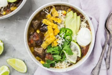 Overhead shot of Slow Cooker Beef Fajita Soup garnished with sliced avocado, cilantro, jalapenos, lime slices, tortilla strips and a dollop of sour cream; with a purple linen, spoons, lime wedges and another bowl of soup arranged around the bowl.