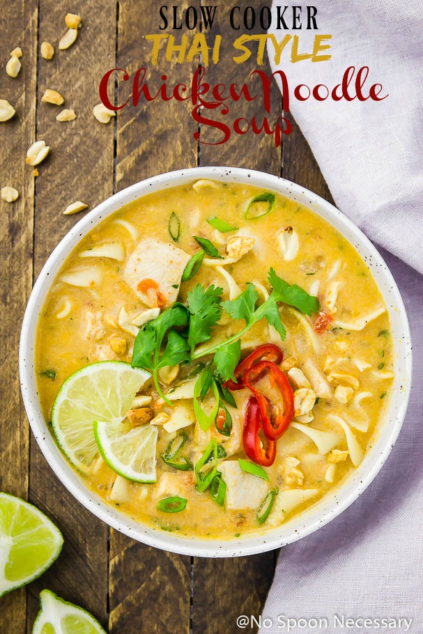 Overhead shot of Slow Cooker Thai Style Chicken Noodle Soup in a white bowl garnished with cilantro, lime wedges and sliced red chilies on a wood table with crushed peanuts, lime wedges and a pale purple linen surrounding the bowl