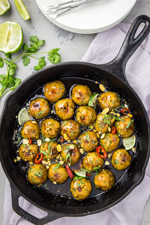 Overhead shot of a large cast iron skillet filled with Sticky Baked Thai Chicken Meatballs with a light lavender linen, stack of small plates, fresh cilantro and lime wedges surrounding the pan.