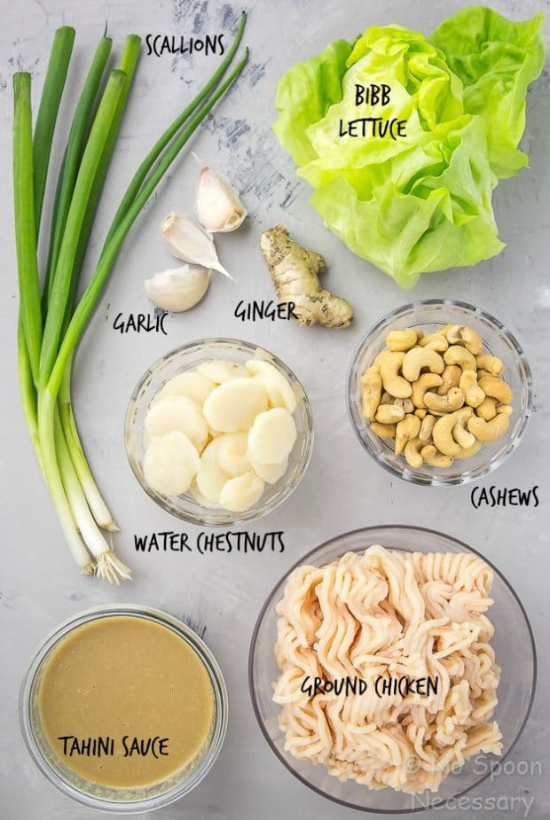 Overhead shot of the ingredients to make Cashew Chicken Lettuce Wraps - scallions, garlic, ginger, bibb lettuce, water chestnuts, cashews, tahini sauce and ground chicken.