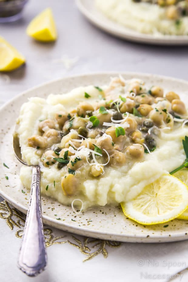 45 degree angle shot of Chickpea Piccata with Cauliflower Mash on a speckled beige plate with a spoon inserted into the 'potatoes' and another plate of piccata, lemon wedges and a small ramekin of capers blurred in the background.