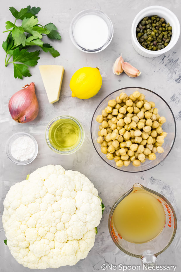 Overhead shot of all the ingredients needed to make Chickpea Piccata recipe and Cauliflower Mock Mashed Potatoes neatly arranged on a gray surface.