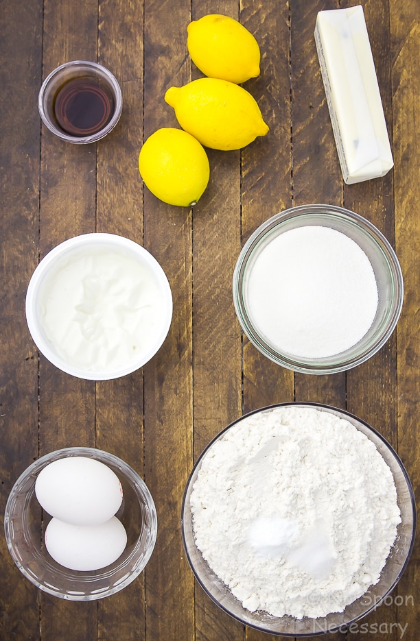 Overhead shot of all the ingredients needed to make Glazed Jumbo Lemon Crumb Muffins neatly organized on a wood surface.