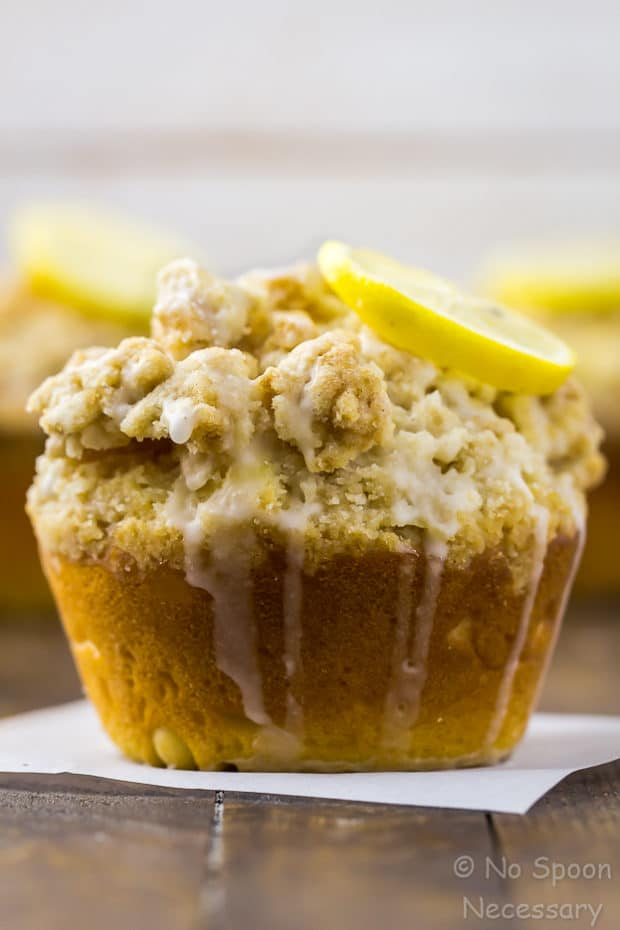Straight on shot of a Glazed Jumbo Lemon Crumb Muffins topped with a lemon slice on a wooden board with more muffins blurred in the background.