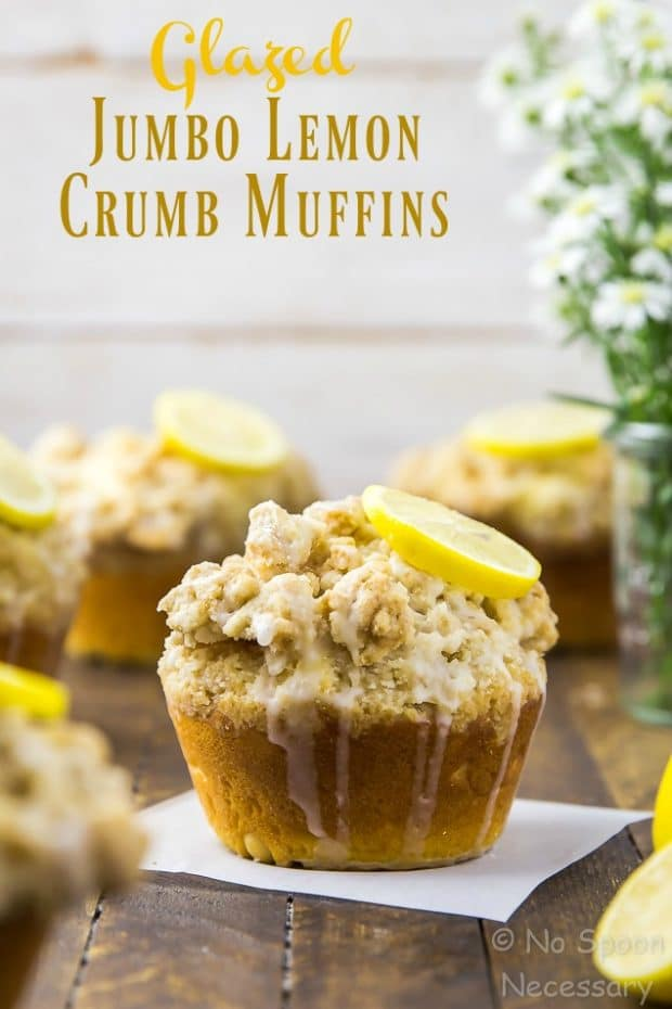 Straight on shot of Glazed Jumbo Lemon Crumb Muffins on a wooden board with spring flowers in the background and the focus of the shot on one individual muffin.