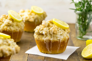 Straight on shot of Glazed Jumbo Lemon Crumb Muffins on a wooden board with spring flowers and lemon halves in the background and the focus of the shot on one individual muffin.