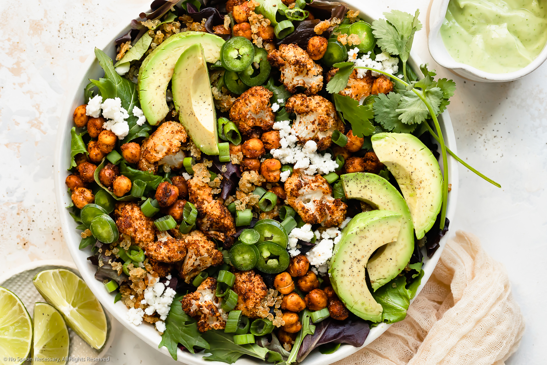 Overhead, landscape photo of Roasted Cauliflower Salad with chickpeas, crispy quinoa and avocado in a large white serving bowl with a ramekin of fresh lime wedges and a jar of avocado dressing next to the bowl.