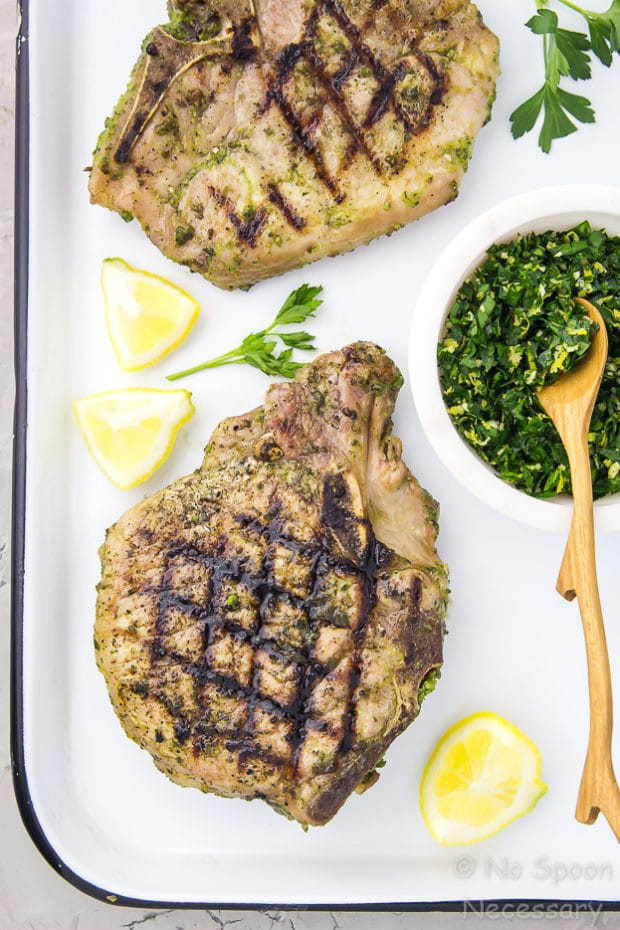 Overhead shot of two grilled Garlic & Herb Pork Chops on a white tray with a ramekin of Gremolata and lemon wedges.
