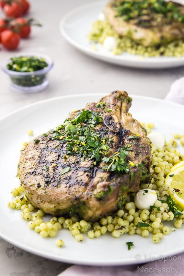 Angled shot of a white plate containing grilled Garlic & Herb Pork Chop topped with Gremolata on a couscous salad with another plate of chops, vine ripe tomatoes, and bowl of gremolata blurred in the background.