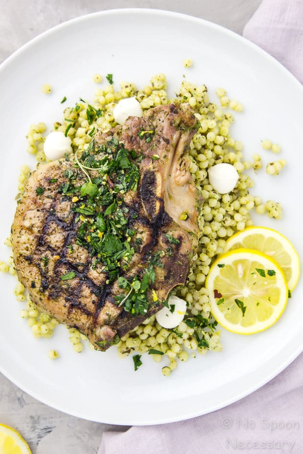 Overhead shot of a white plate containing grilled Garlic & Herb Pork Chop topped with Gremolata on a couscous salad with a purple linen under the plate.
