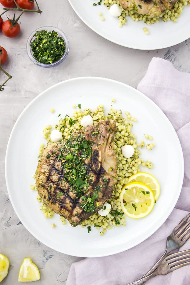 Overhead shot of a white plate containing grilled Garlic & Herb Pork Chop topped with Gremolata on a couscous salad with a purple linen, forks, vine ripe tomatoes, and bowl of gremolata surrounding the plate.