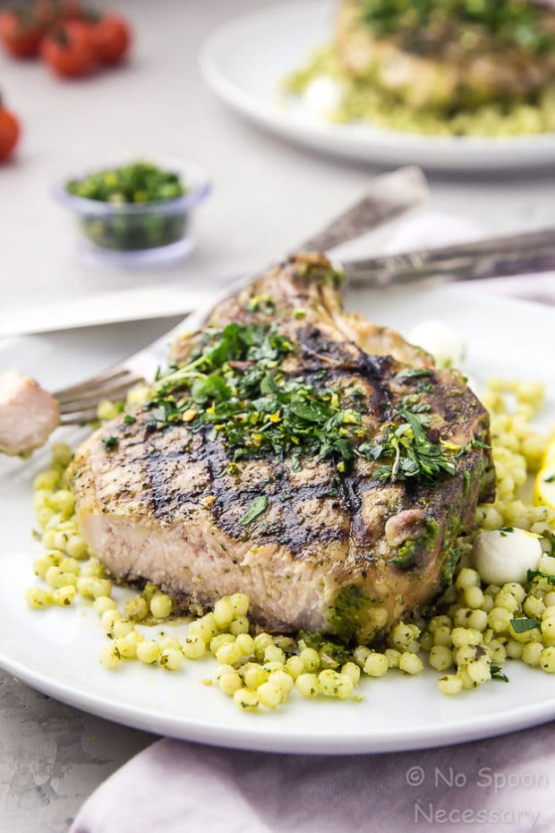 Angled shot of a white plate containing a cut into grilled Garlic & Herb Pork Chop topped with Gremolata on a couscous salad with another plate of chops, vine ripe tomatoes, and bowl of gremolata blurred in the background.