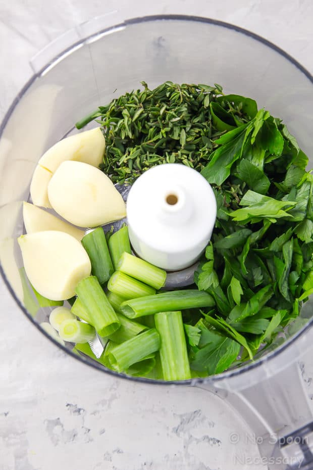 Overhead shot of the inside of a food processor bowl filled with the ingredients needed to make Gremolata, which is the garnish for Garlic & Herb Pork Chops recipe.