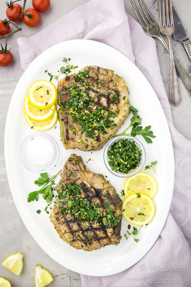 Overhead shot of two Garlic & Herb Pork Chops topped with Gremolata on a white platter with lemon slices and fresh parsley; with a pale purple napkin under the platter and vine ripe tomatoes, forks and lemon wedges surrounding the platter.