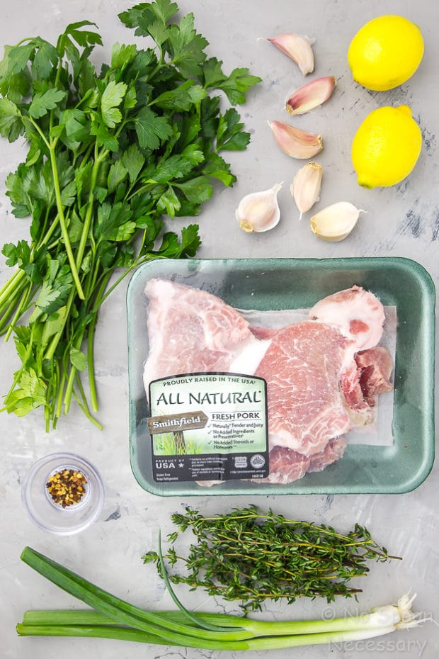 Overhead shot of all the ingredients needed to make Garlic & Herb Pork Chops with Gremolata recipe neatly organized on a gray surface.