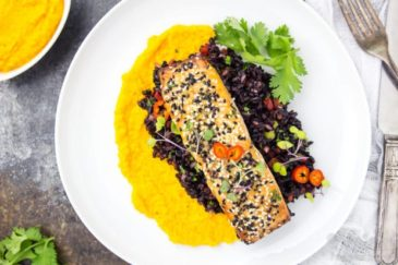 Overhead, landscape shot of Honey Sesame Salmon & Asian Black Rice Salad with carrot-ginger sauce on a white plate garnished with fresh cilantro.