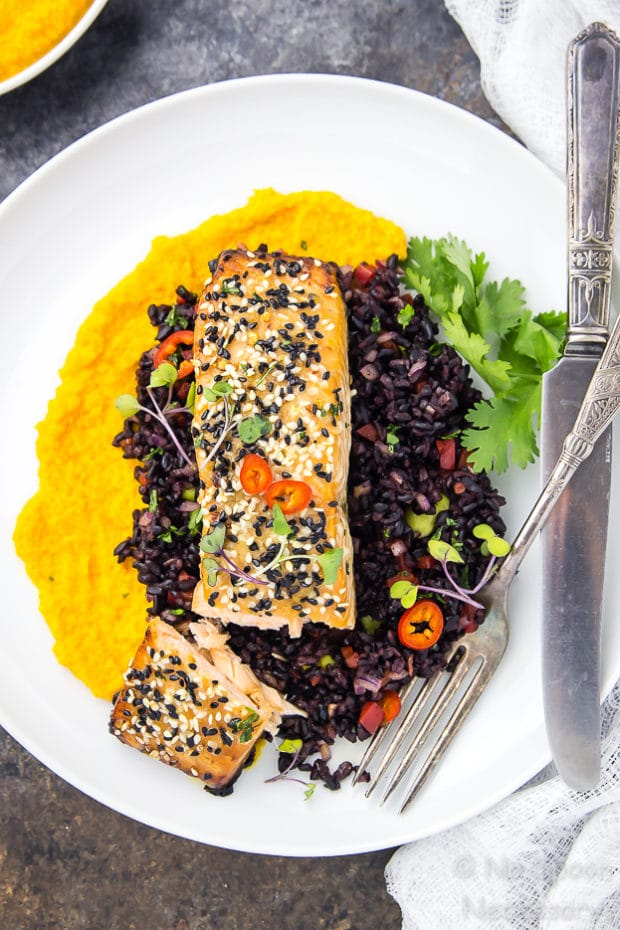 Overhead shot of cut into Honey Sesame Salmon & Asian Black Rice Salad with carrot-ginger sauce on a white plate garnished with a knife and fork.