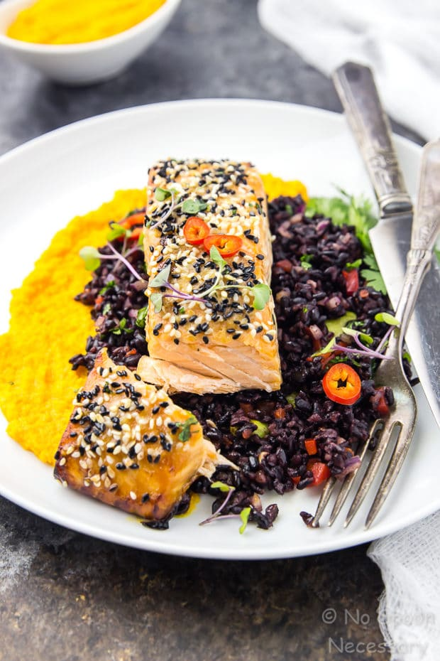 Angled shot of cut into Honey Sesame Salmon & Asian Black Rice Salad with carrot-ginger sauce on a white plate with a knife and fork.