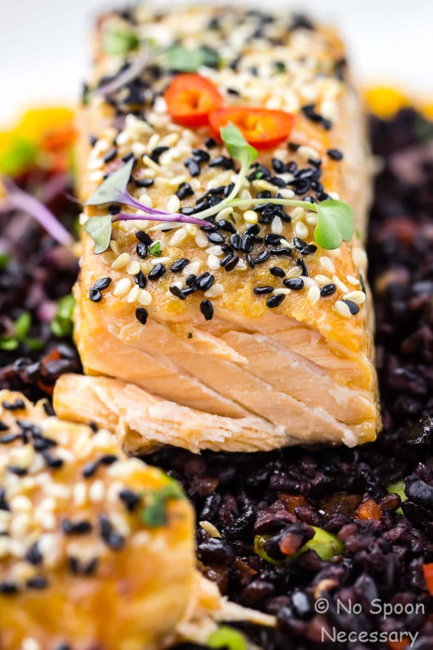 Angled, extreme up close shot of cut into Honey Sesame Salmon served on top of Asian Black Rice Salad.