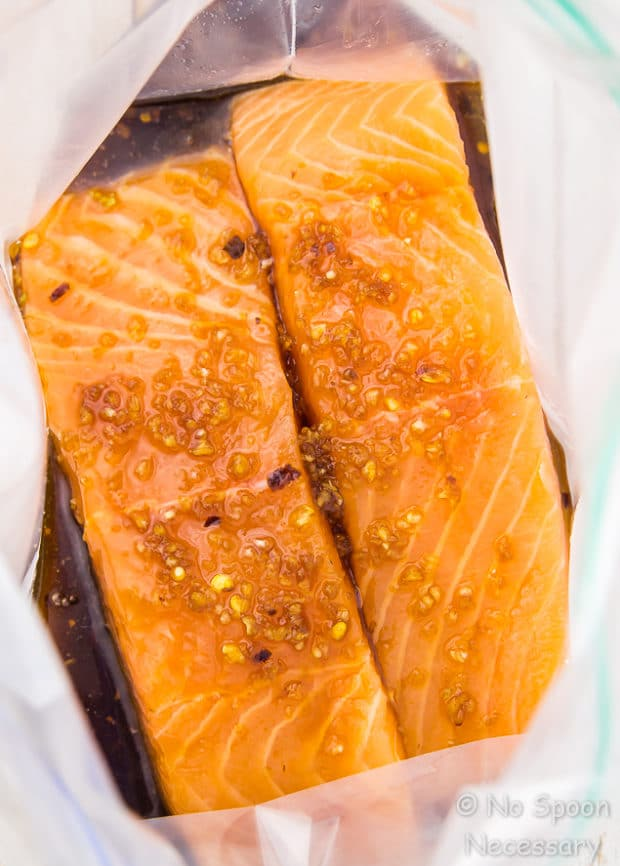 Overhead shot of two filets of raw salmon with honey ginger marinade in a zip-closure bag - first step in the recipe to make Honey Sesame Salmon.