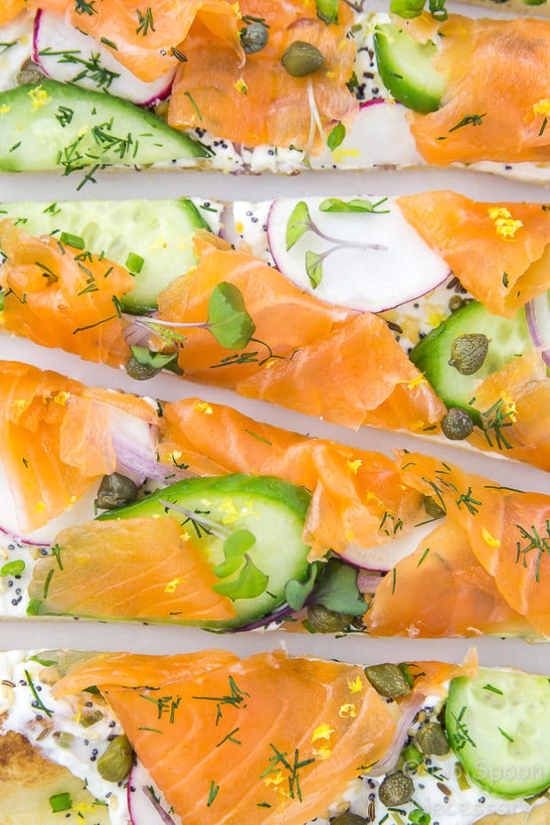 Overhead, up close shot of Loaded Spring Salmon Pizza that has been cut into slices.