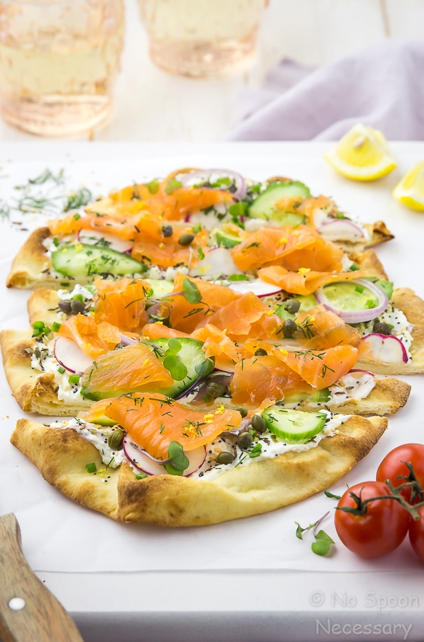 Angled shot of Loaded Spring Salmon Pizza that has been cut into slices on a white board with a wooden handled knife, fresh dill, vine ripe tomatoes and two peach colored water glasses surrounding the pizza.