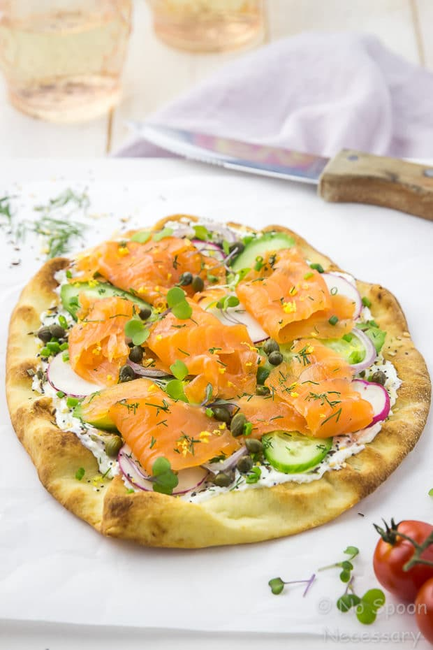 Angled shot of Loaded Spring Salmon Pizza on a white board with a wooden handled knife, fresh dill, vine ripe tomatoes and two peach colored water glasses surrounding the pizza.