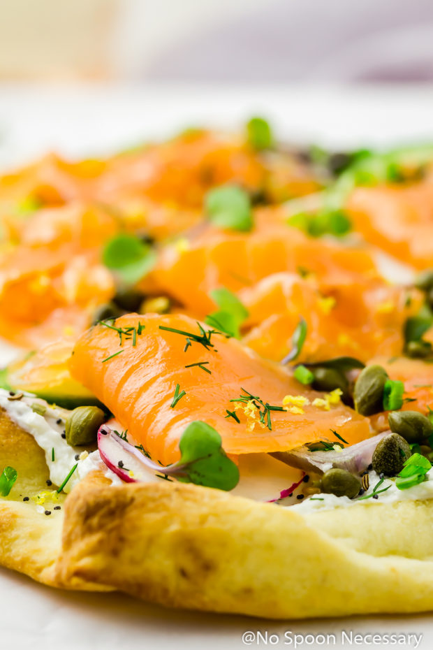 Angled shot of Loaded Spring Salmon Pizza with the focus of the shot on the gravlax topping the pizza.