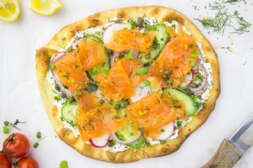 Overhead, landscape shot of Loaded Spring Salmon Pizza on a white surface with a wooden handled knife, fresh dill and vine ripe tomatoes surrounding the pizza.