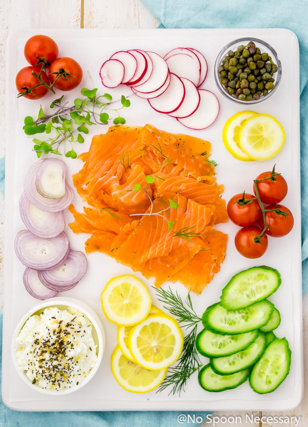 Overhead shot of a white board on a pale blue linen neatly topped and organized with an array of cured salmon gravlax, sliced shallots, vine ripe tomatoes, sliced radishes, sliced lemons, sliced cucumbers, a small bowl of capers, fresh herbs and a bowl of everything spice cream cheese.
