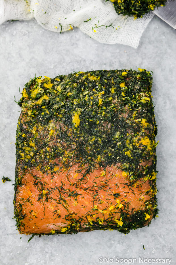 Overhead shot of a filet of salmon that has been cured, with part of the dry brine scrapped off the top - step 8 of how to make gravlax, or cured salmon.
